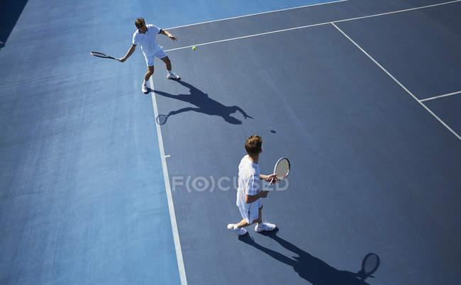 Юные теннисисты играют в теннис на солнечно-синем теннисном корте — стоковое фото