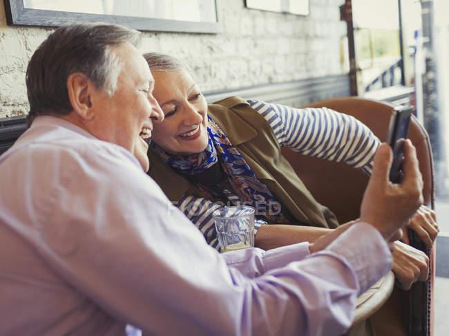 Улыбаясь старший пара принимая selfie с камеры телефона на столе кафе — стоковое фото