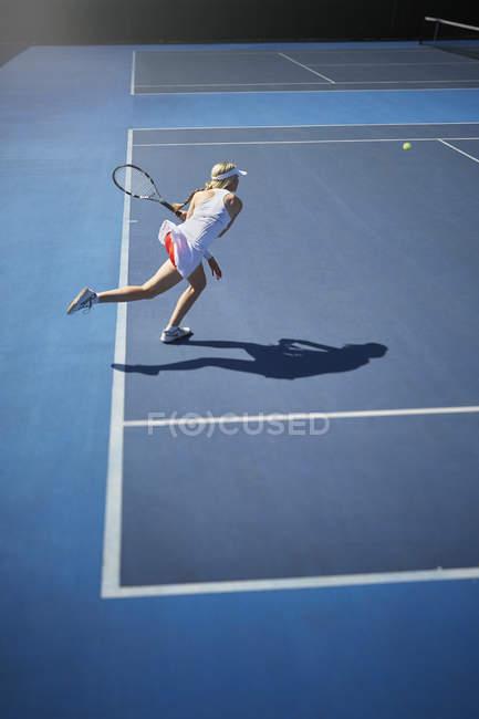 Молодая теннисистка играет в теннис, размахивая теннисной ракеткой на солнечном синем теннисном корте — стоковое фото