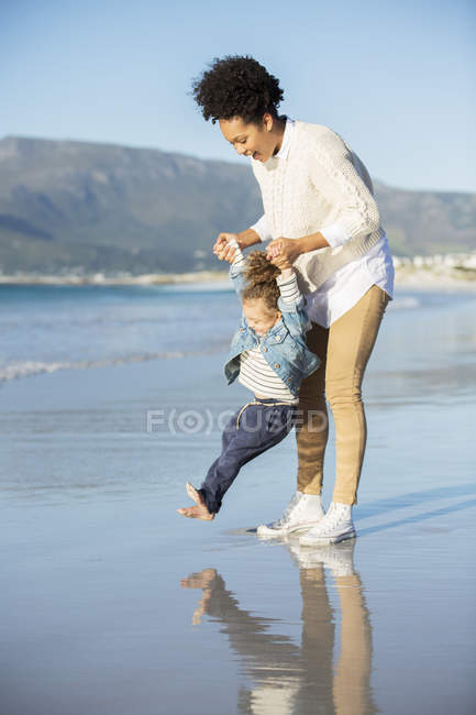 Mother and daughter playing on beach — Stock Photo