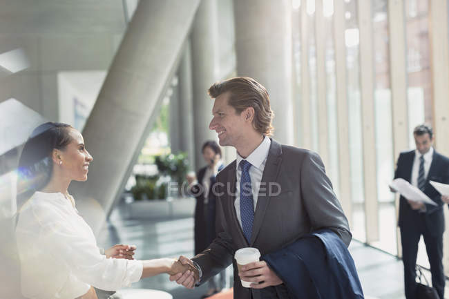 Businessman and businesswoman handshaking in sunny office lobby — Stock Photo