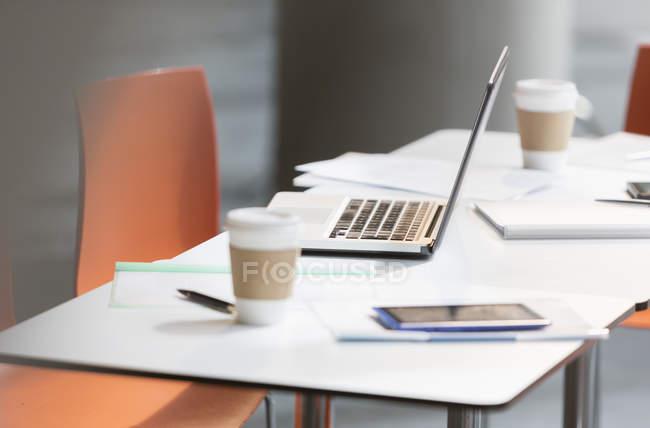 Computer portatile, caffè e scartoffie sul tavolo in ufficio — Foto stock