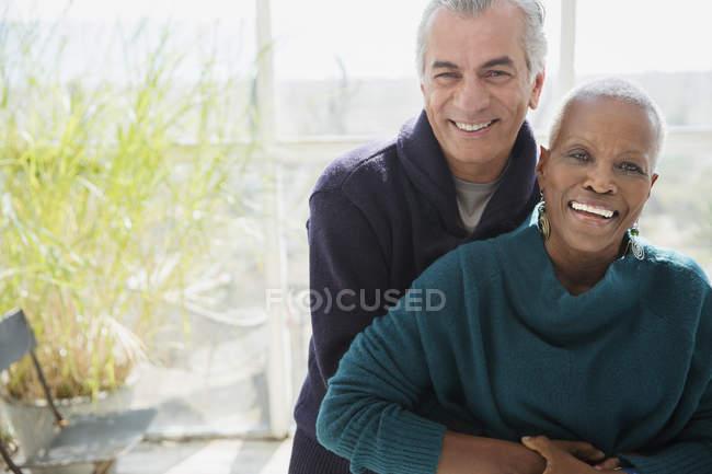 Retrato sorrindo casal sênior abraçando no alpendre sol — Fotografia de Stock