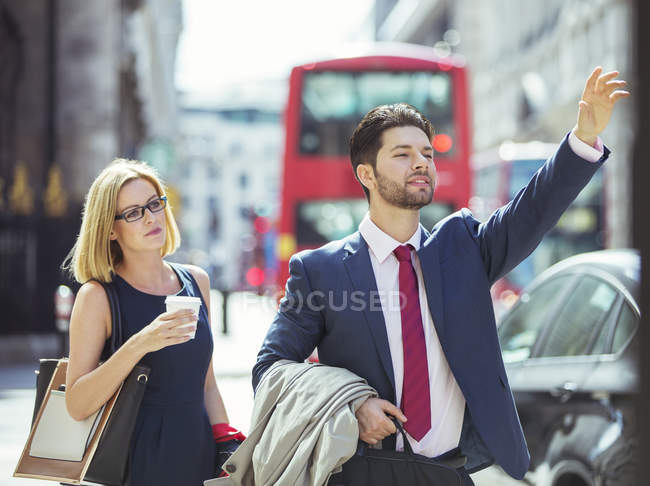 Business people hailing taxi in city — Stock Photo