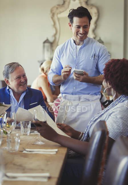 Camarero teniendo orden de pareja con menús en el restaurante de mesa - foto de stock