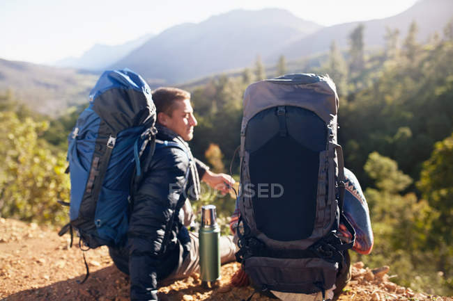 Young couple with backpacks hiking, taking a coffee break — Stock Photo