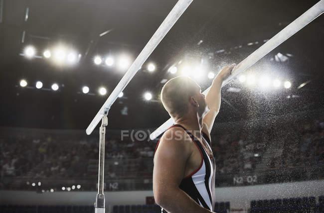 Male gymnast applying chalk powder to parallel bars — Stock Photo