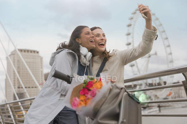 Enthusiastic, smiling women friends taking selfie with camera phone near Millennium Wheel, London, UK — Stock Photo