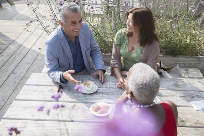 Amigos maduros hablando y tomando café en la mesa del patio - foto de stock