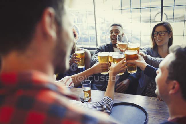 Amigos comemorando, brindando o copo de cerveja na mesa de bar — Fotografia de Stock
