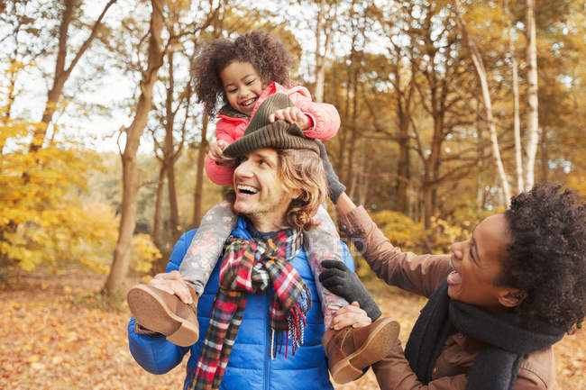 Playful young family in autumn park — Stock Photo
