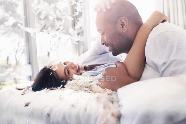 Plumas de almohada cayendo alrededor pareja juguetona, cariñosa en la cama - foto de stock