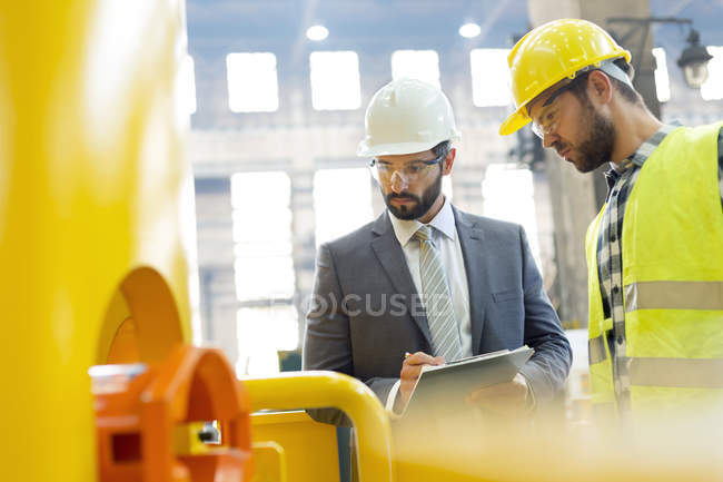Manager and steel worker examining equipment in factory — Stock Photo