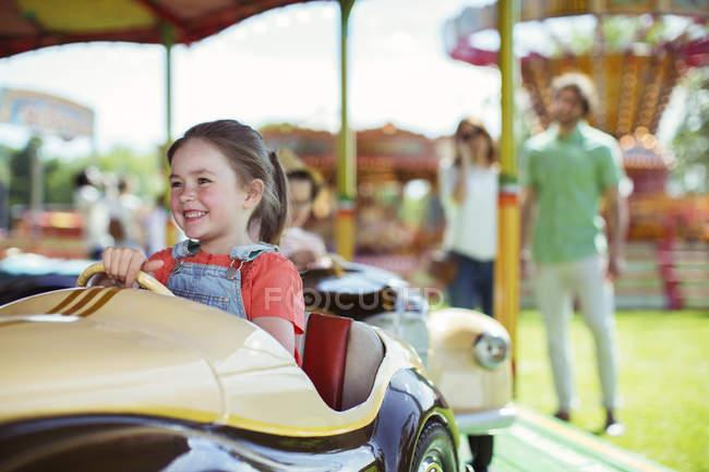 Fille joyeuse sur carousel en parc d'attractions — Photo de stock