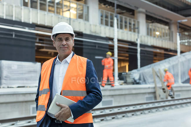 Portrait confident engineer with digital tablet at construction site — Stock Photo