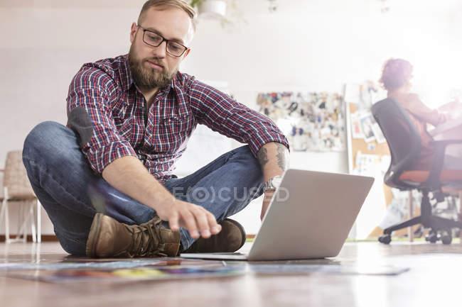 Diseño masculino pruebas de revisión profesional en el ordenador portátil en el piso de la oficina - foto de stock