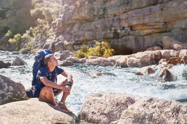 Giovane con lo zaino escursionismo, riposa al flusso luminoso, scoscesa — Foto stock
