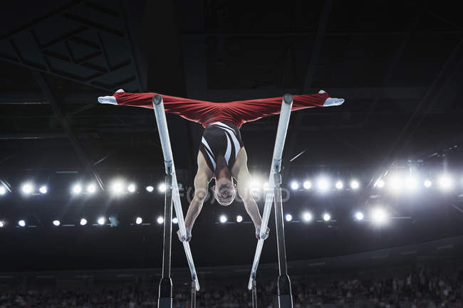 Male gymnast performing upside-down splits on parallel bars in arena — Stock Photo
