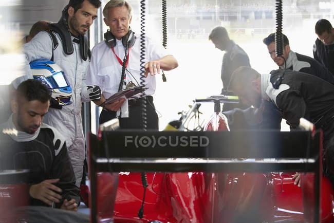 Gerente e um motorista de fórmula assistindo pit crew trabalhando em carro de corrida na garagem de reparação — Fotografia de Stock