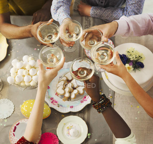 Overhead view friends toasting champagne glasses over Easter desserts — Stock Photo