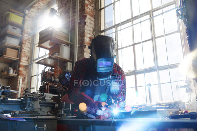 Welder welding with welding mask and torch in workshop — Stock Photo