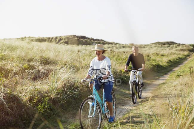 Зрелая пара катается на велосипедах по солнечной травяной дорожке — стоковое фото