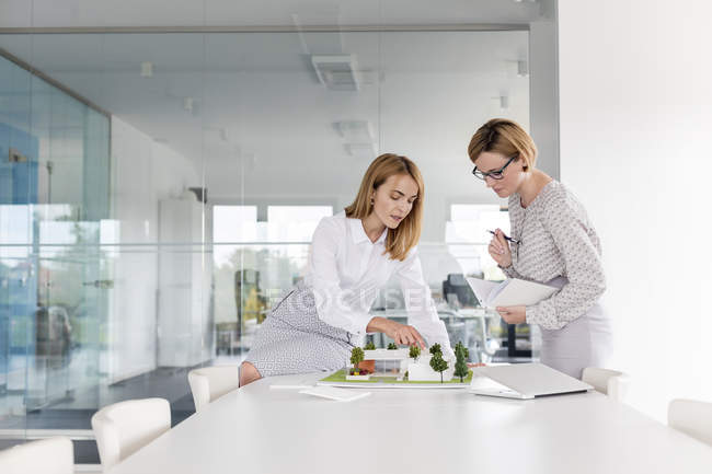 Female architects discussing model in conference room meeting — Stock Photo