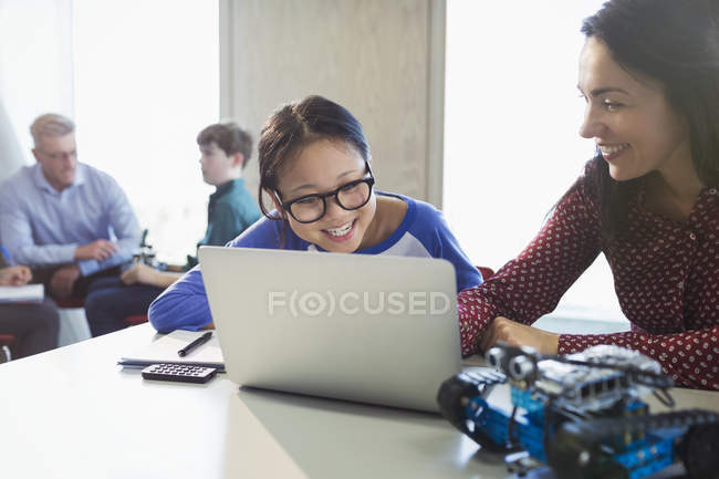 Female teacher and girl student programming robotics at laptop in classroom — Stock Photo