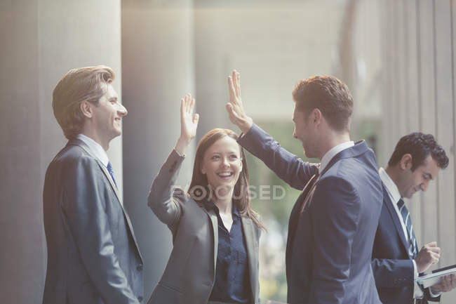 Business people high-fiving in office lobby — Stock Photo