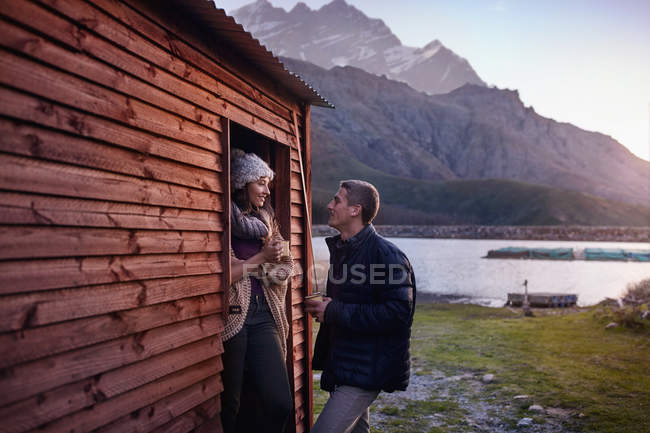 Young couple drinking coffee at lakeside cabin doorway — Stock Photo