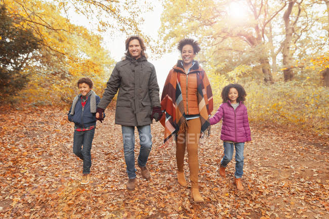 Portrait smiling young family holding hands walking on path in autumn park — Stock Photo