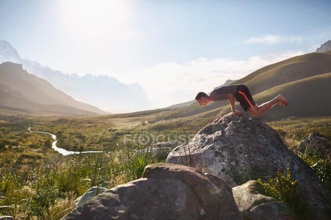 Молодой человек балансирует на руках на скале в солнечной, отдаленной долине — стоковое фото
