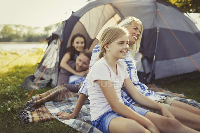 Smiling family relaxing outside campsite tent — Stock Photo