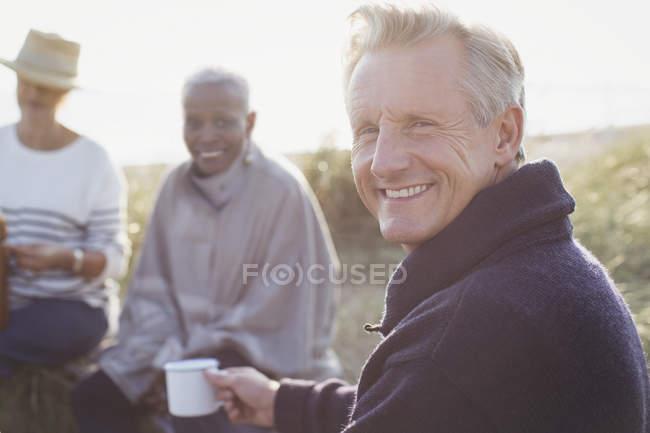 Porträt lächelnder älterer Mann trinkt Kaffee mit Freunden am sonnigen Strand — Stockfoto