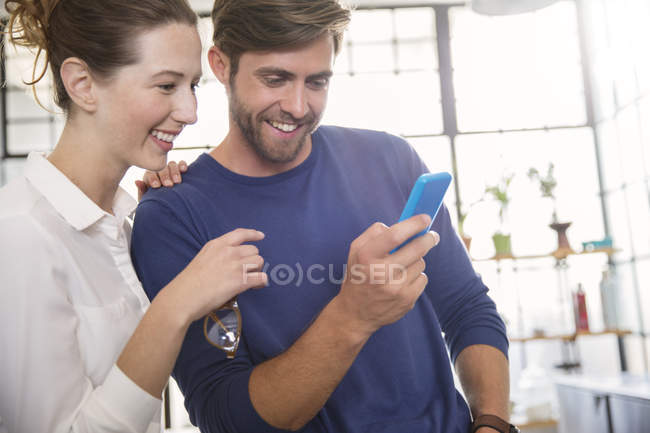 Two young people looking at mobile phone and smiling — Stock Photo