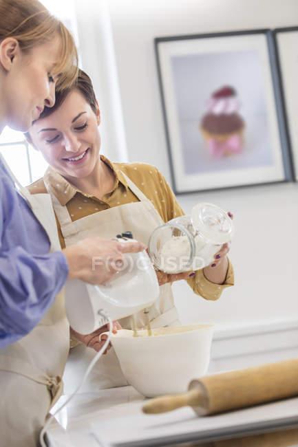 Femmes de cuisson, en utilisant un mélangeur électrique à main dans la cuisine — Photo de stock