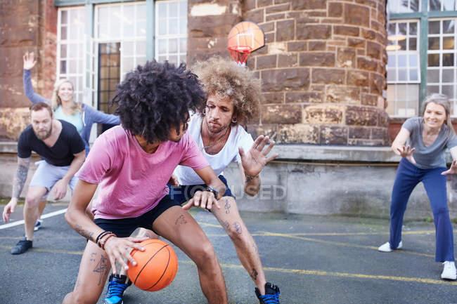 Друзья играют в баскетбол на городской баскетбольной площадке — стоковое фото