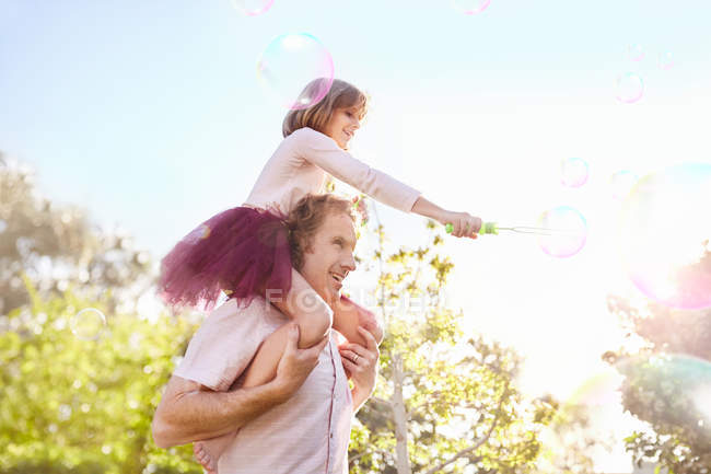Father carrying daughter with bubble wand on shoulders in sunny summer park — Stock Photo