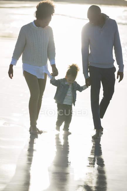 Familia feliz caminando en la playa - foto de stock