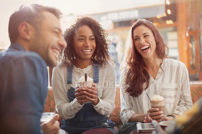 Laughing young friends drinking milkshakes in cafe — Stock Photo