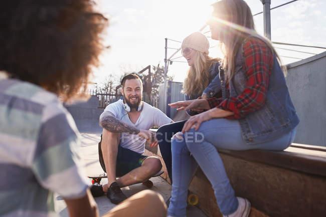Amici con skateboards hanging out e ne al sole skate park — Foto stock