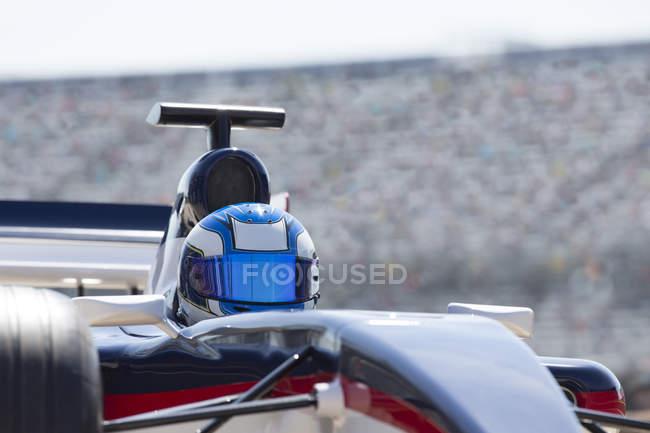 Formel 1 Rennfahrer mit Helm am Sportplatz — Stockfoto