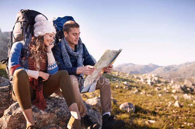 Jeune couple avec sacs à dos de randonnée, de repos et de vérifier la carte sur les rochers ensoleillés — Photo de stock