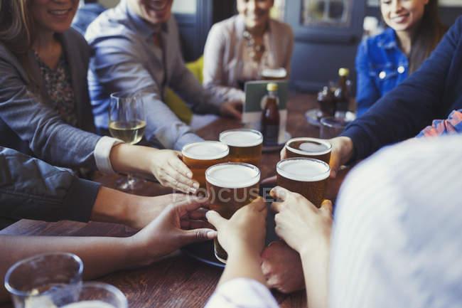 Freunde greifen auf Stehtisch nach Biergläsern — Stockfoto