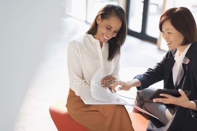 Donne d'affari sorridenti che rivedono documenti in ufficio soleggiato — Foto stock