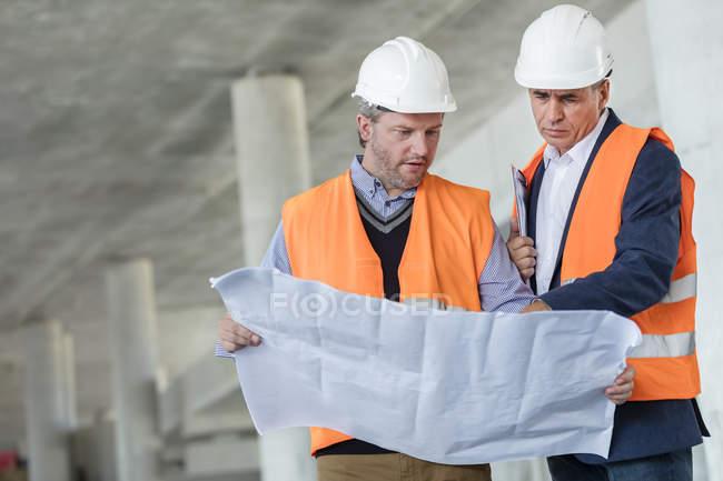 Инженеры-мужчины изучают подземные чертежи на строительной площадке — стоковое фото