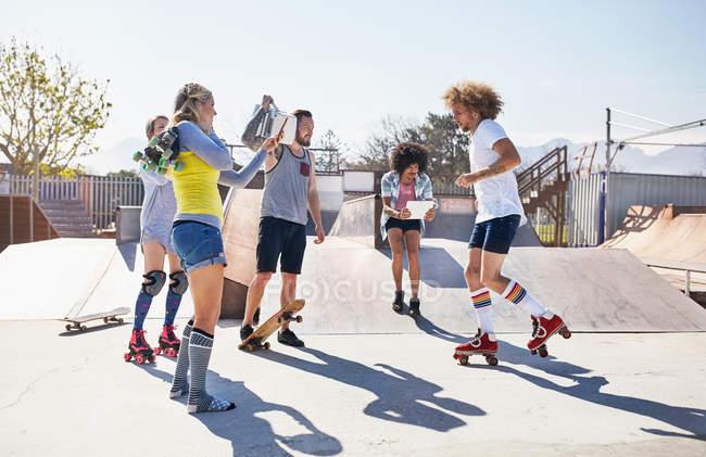 Amici pattinaggio a rotelle e skateboard al soleggiato skate park — Foto stock