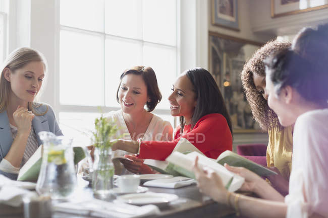 Women friends discussing book club book at restaurant table — Stock Photo