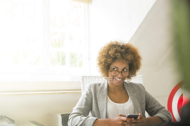 Portrait of smiling office worker with smart phone — Stock Photo