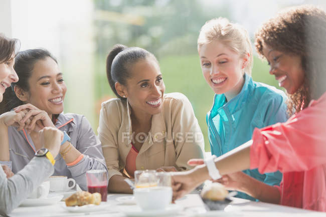Women talking and looking at smart watch at cafe table post workout — Stock Photo